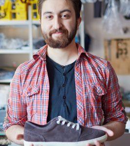 Portrait of a handsome man selling footwear in sports shop